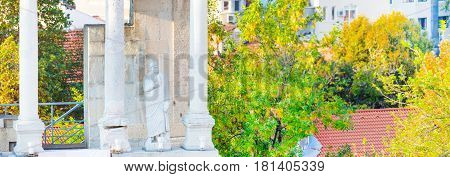 Panoramic banner background with statue, column and fragment of ancient roman amphitheater, Plovdiv, Bulgaria