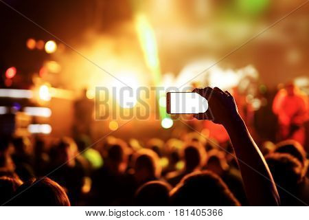 Hands with a smartphone records live music festival, live concert, show on stage