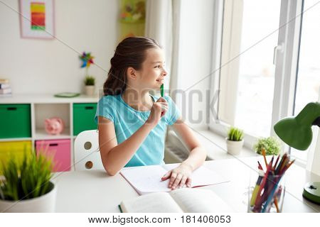 people, children, education and learning concept - happy girl with book and notebook doing homework and looking through window at home