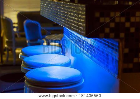 Empty bar stools along bar Illuminated in blue purple light