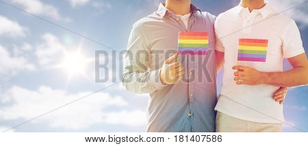 people, homosexuality, same-sex marriage and love concept - close up of happy male gay couple hugging and holding rainbow flags over sky and sun background