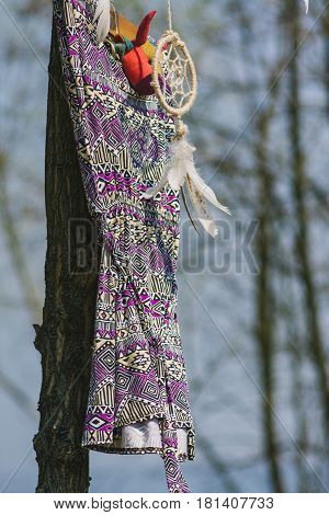 On the tree hanging dream catcher and a woman's dress. Indie style.