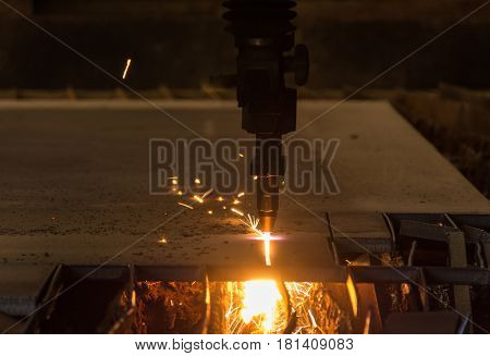 Metal cutting with acetylene torch by auto cutting machine close-up on low light