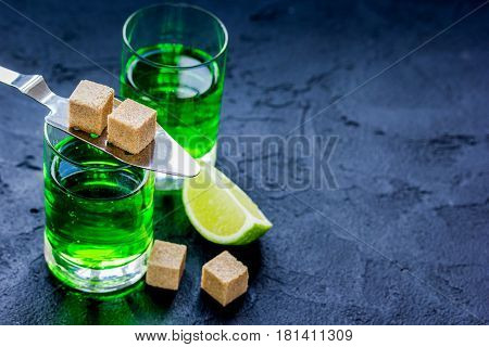 green absinthe with sugar cubes in spoon on dark table background mock up