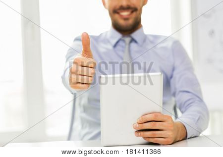 business, people and technology concept - smiling businessman with tablet pc computer showing thumbs up at office
