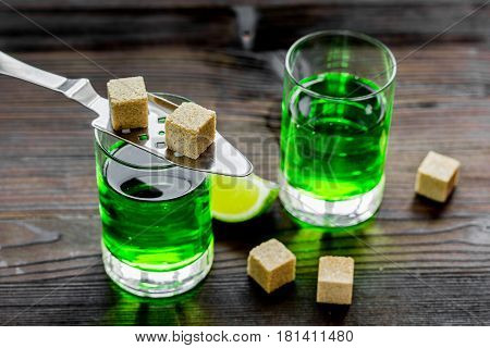 absinthe shots with fresh green lime slices and sugar cubes on wooden bar table background