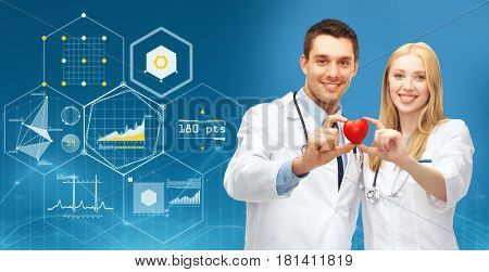 healthcare, people, cardiology and medicine concept - smiling doctors with red heart over blue background and virtual charts