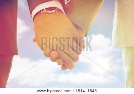 people, homosexuality, same-sex marriage and love concept - close up of happy male gay couple holding hands with wedding rings on over sky and sun background