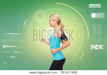 fitness, sport, people, exercising and technology concept - happy young woman running with earphones and smartphone and listening to music over green background