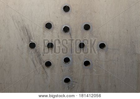 Metal plate with many circular holes background. macro