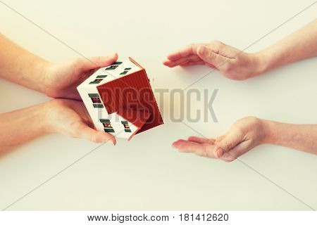 charity, building, sale, real estate and property concept - close up of hands giving and receiving house or home model