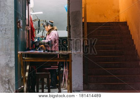 Chongqing CHINA - 22 Dec 2015: A chinese women tailor entrepreneur sewing behind an old machine in a street beside stairs