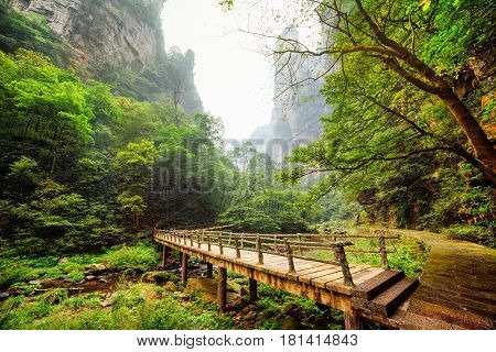 Amazing View Of Wooden Bridge Over River At Bottom Of Deep Gorge