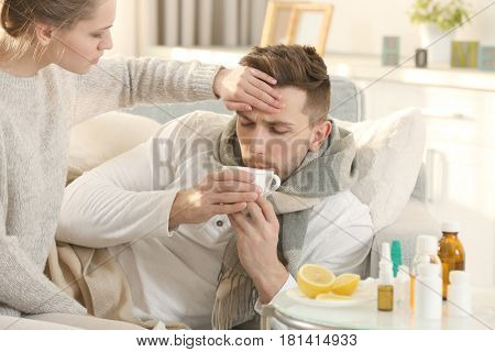 Young woman taking care of ill man lying on sofa at home