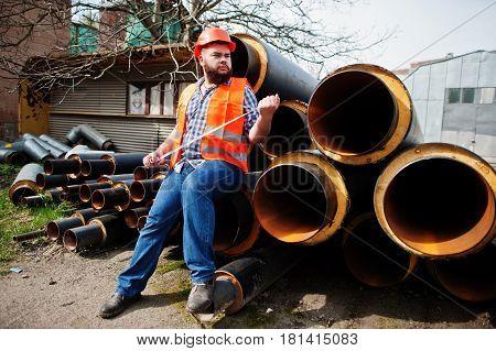 Brutal Beard Worker Man Suit Construction Worker In Safety Orange Helmet Near Steel Pipes With Tape