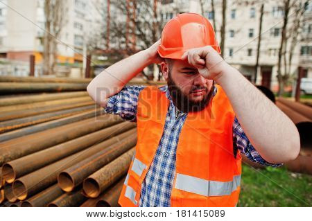 Brutal Beard Worker Man Suit Construction Worker In Safety Orange Helmet Near Steel Pipes.