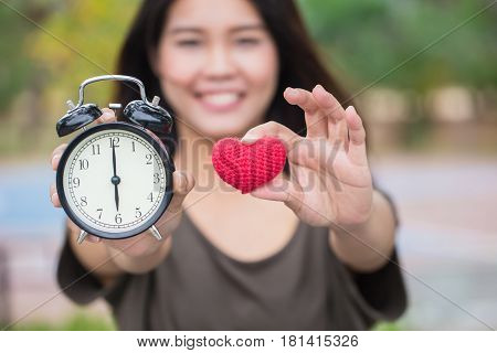 giving love and time in valentine's day. Asian women hand show red heart and clock times at 6 o'clock It's time to loving together.