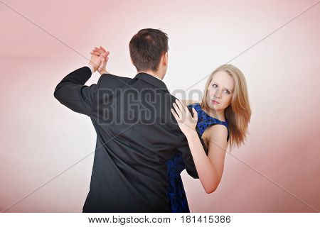 Blond girl in a dress dancing with a guy in a suit