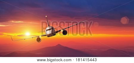 Commercial jet airplane flying above mountains in beautiful sunset light. Front view of cabin. Air travel and vacation concept.