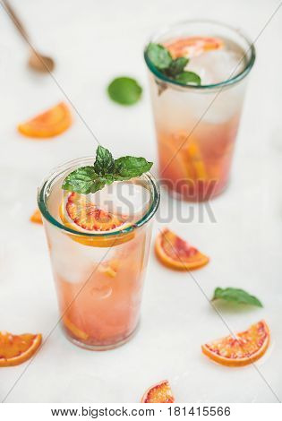 Blood orange fresh summer homemade lemonade with ice and mint in glasses, light grey marble background, selective focus