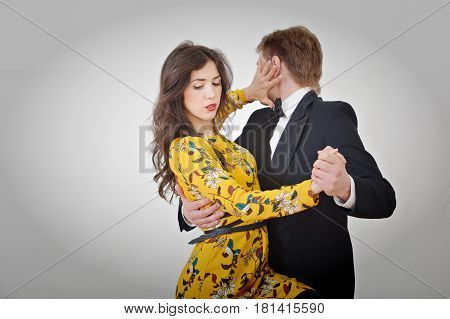 Brunette girl in a yellow dress dancing with a guy in a suit