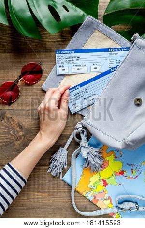 journey planning with tourist outfit and hand, glasses, flight tickets on wooden table background top view