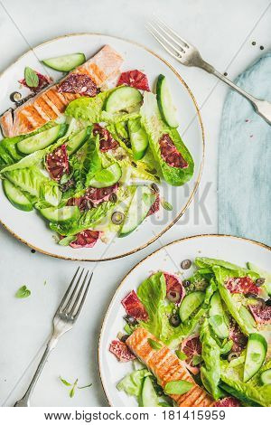 Healthy energy boosting spring salad with grilled salmon, blood orange, olives, cucumber and quinoa, top view, marble background. Clean eating, dieting, detox, weight loss concept