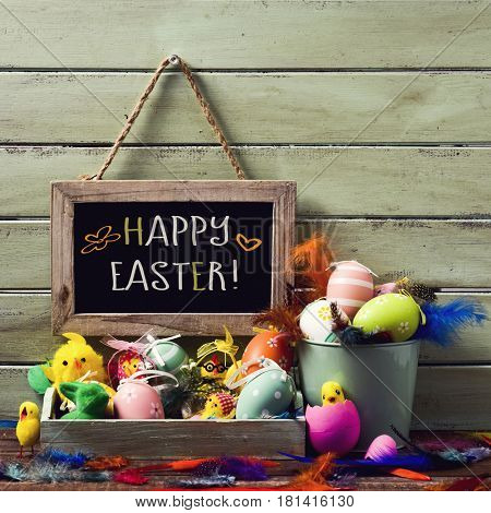 a wooden-framed chalkboard with the text happy easter hanging on a rustic wooden wall, and a pile of different decorated easter eggs, some teddy chicks and feathers of different colors