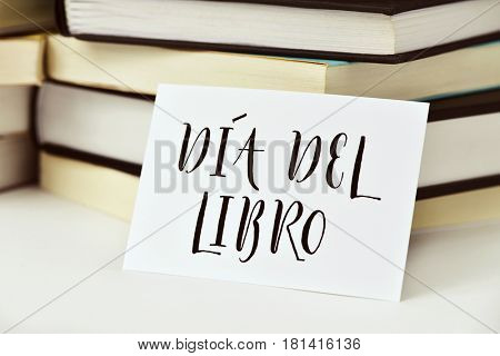 closeup of a piece of paper with the text dia del libro, book day written in spanish, in front of a pile of books, placed on a white surface