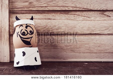 brown egg with a funny face disguised as a cow, with a head band with cow horns, against a rustic wooden surface with a blank space