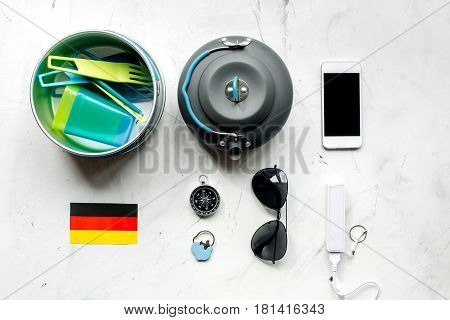 Outfit for trip with german flag and mobile phone on white table background top view