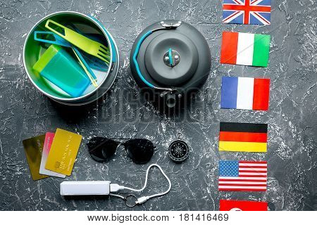 Outfit of traveller with flags and credit cards on gray table background top view