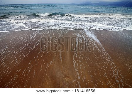Sea beach with waves in gray day. Wide angle view.