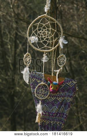 On the tree hanging dream catcher and a woman's dress. Hipster style.