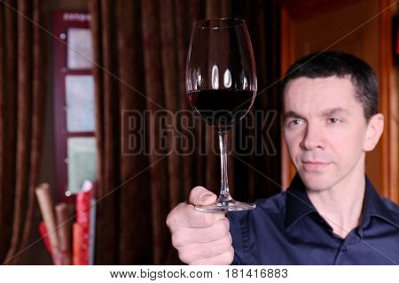 Handsome man holding glass of red wine