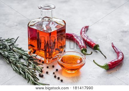 natural oils concept with fresh chili paper and glass jar on stone table background