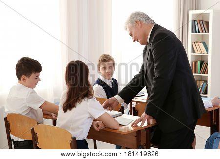 Senior teacher explaining exercise to pupils in classroom