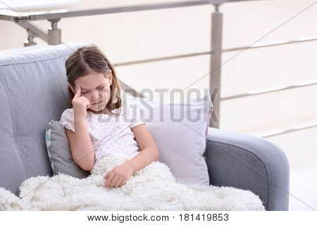 Little girl suffering from headache at home