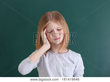 Cute girl suffering from headache on color background