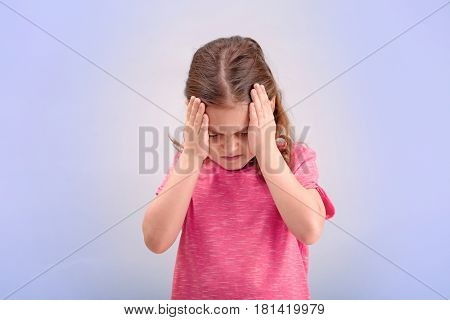 Little girl suffering from headache on color background