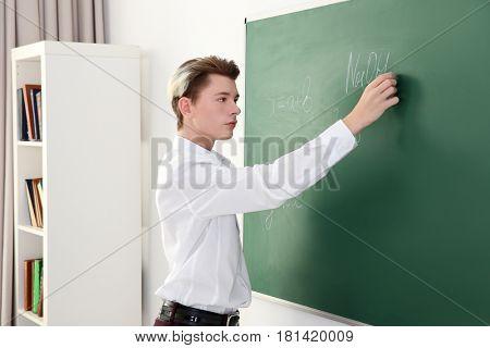 Schoolboy answering at blackboard in classroom