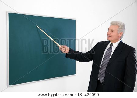Senior teacher with pointer standing near blackboard