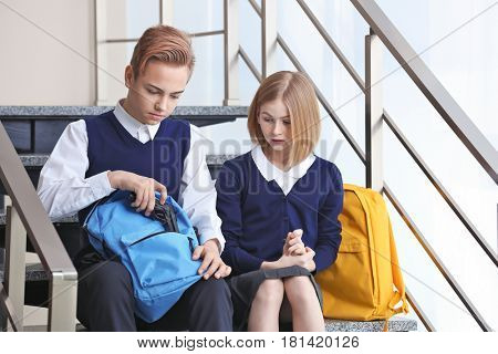 Schoolboy sitting on school stairs with friend and showing gun