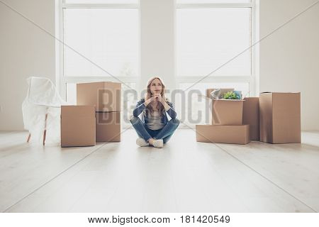 Dream Come True! Portrait Of Young Pretty Woman Sitting On The Floor And Thinking How To Unpack All
