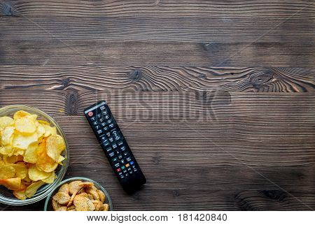 snacks for watching TV film with control on wooden desk background top view mock-up