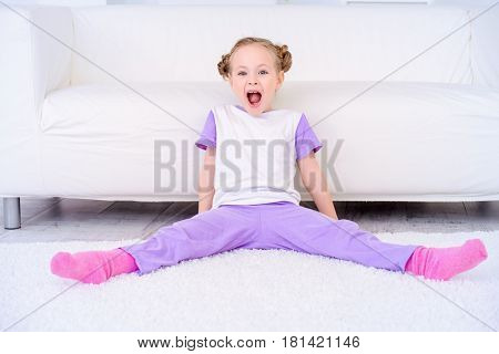 Cute emotional girl sitting on a carpet at home and shouting.