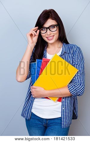 Portrait Of Happy Student Girl In Glasses Holding Notebooks In Hands