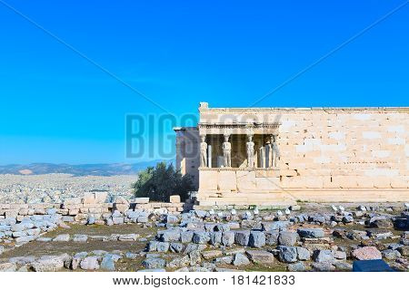 panoramic background with Acropolis, porch of caryatids, Erechtheum Temple in Athens, Greece and blue sky