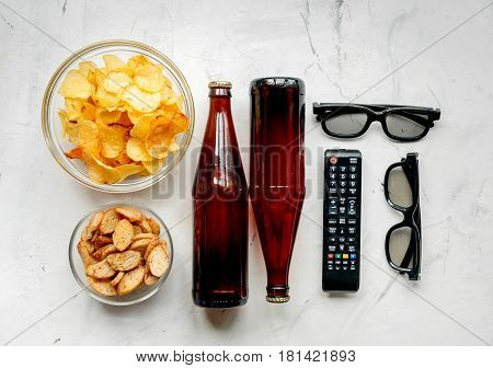 watching movies concept with chips, beer and zapper on white table background top view mock-up
