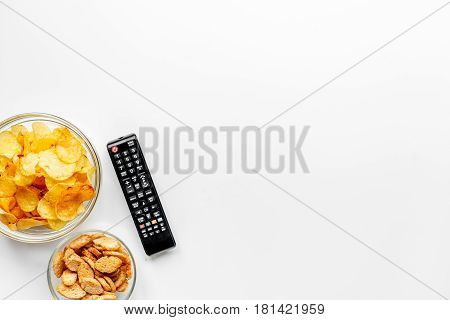 TV remote control and snacks on white desk background top view space for text